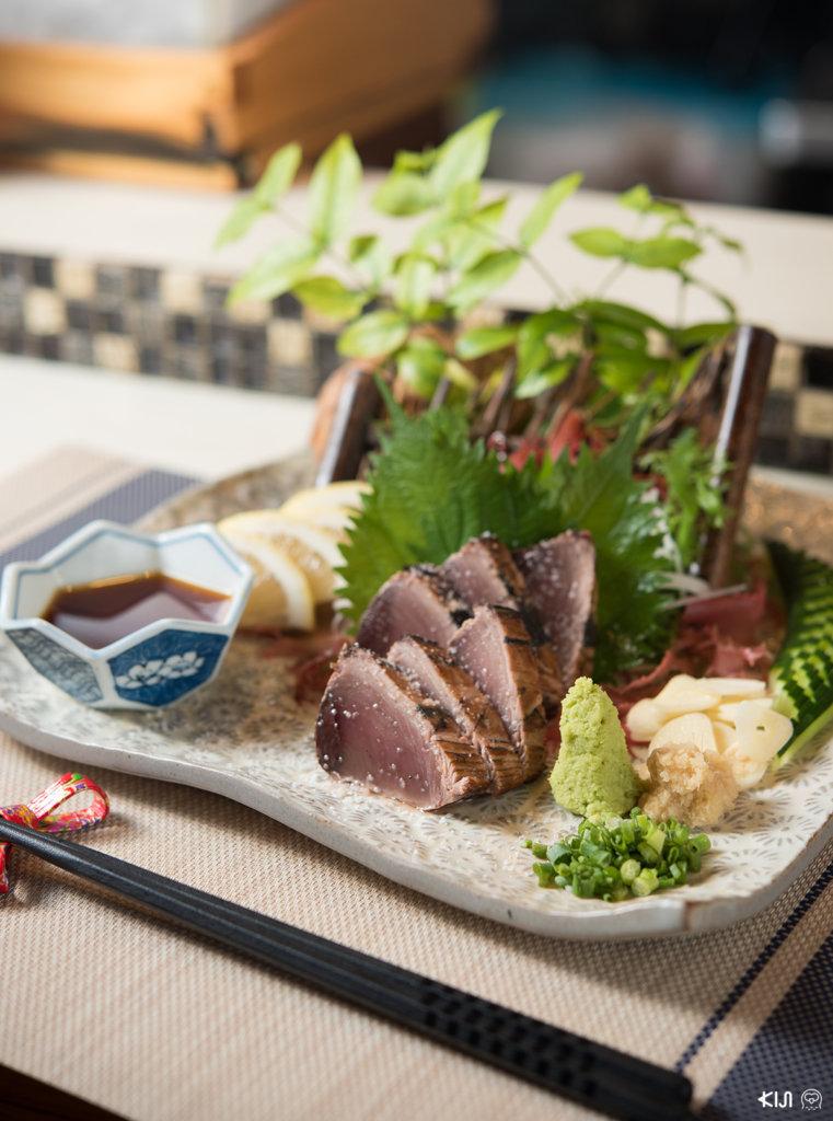 เมนู Katsuo Shio Warayaki : นำปลาที่ย่างมา ตกแต่งใส่จานอย่างสวยงามพร้อมโรยเกลือเล็กน้อยเพิ่มรสชาติ วางเครื่องเคียง ขิง กระเทียม ต้นหอม วาซาบิ และน้ำจิ้มพอนสึให้กินคู่กัน
