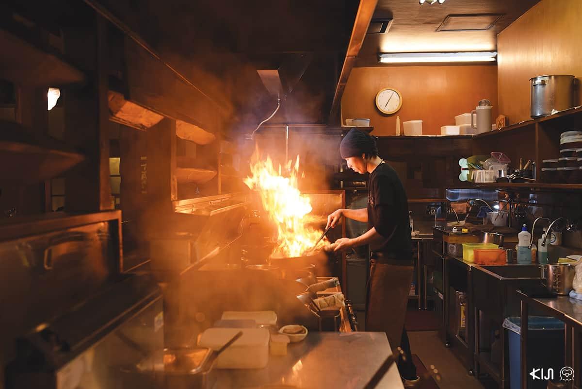 เชฟของร้าน YOSHIYAMA SHOTEN กำลังปรุงอาหาร