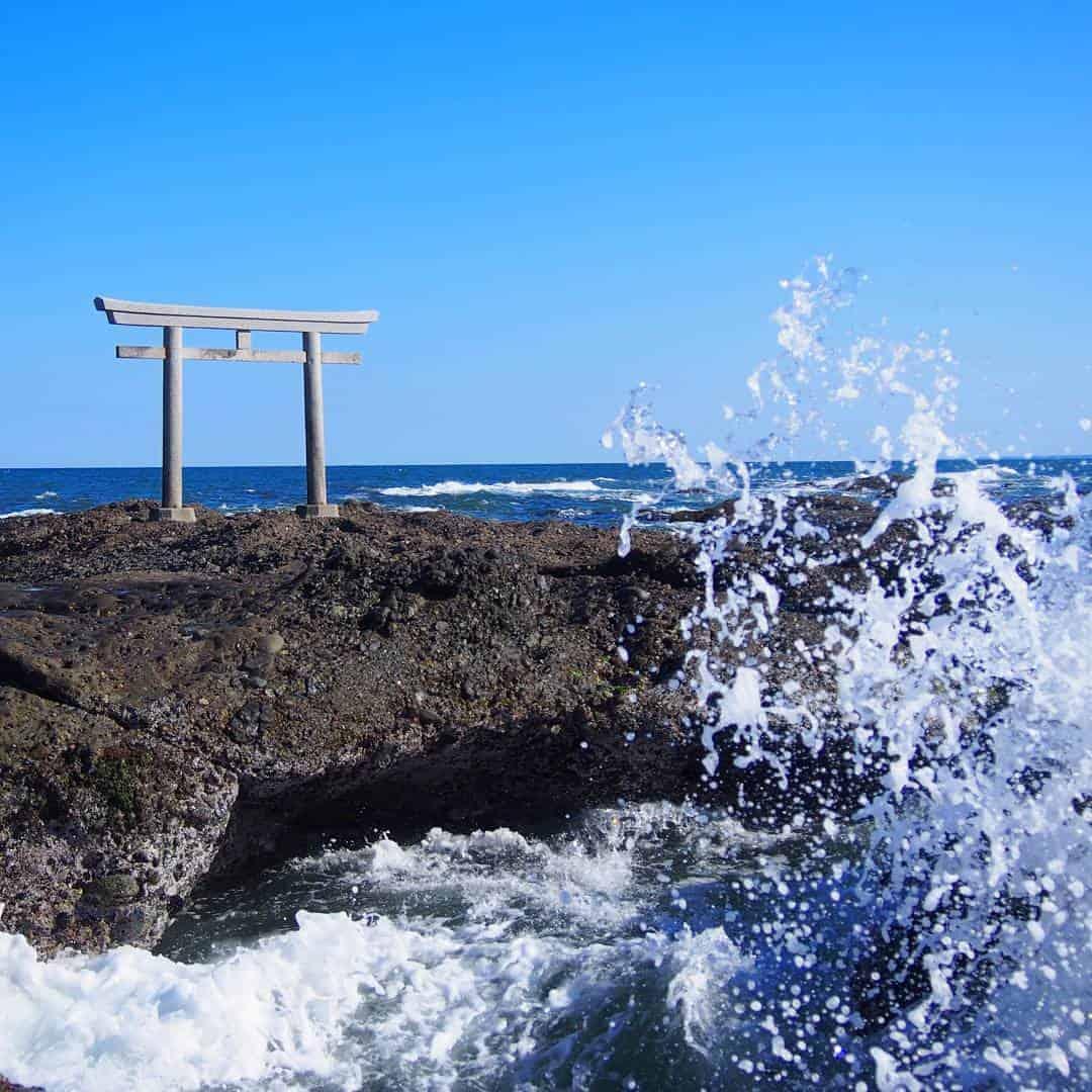 ฟองคลื่นที่ดีดกระเซ็นสูงจากผิวน้ำกับโทริอิสีเทาที่นิ่งสงบ