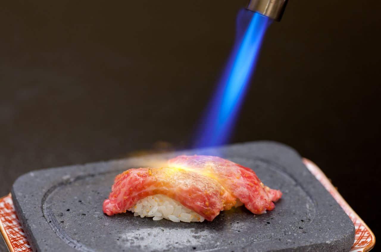 การลนไฟ/อาบุริเพื่อให้เนื้อวัวด้านบนสุก จนเกิดเป็นซูชิที่กึ่งสุกกึ่งดิบ