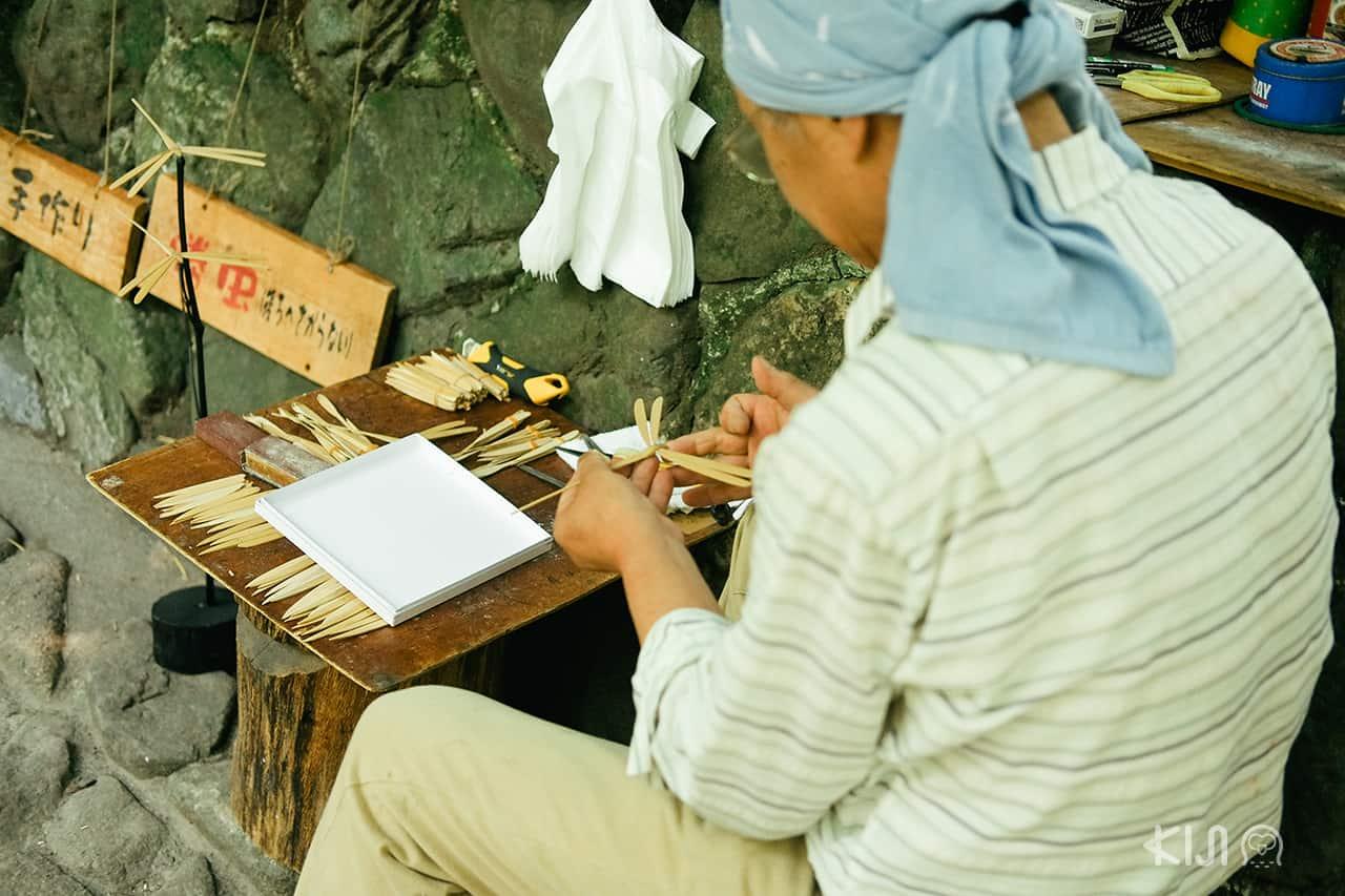 คุณลุงนั่งประดิษฐ์ของทำมืออยู่ตามข้างทางที่ Kyoto Sagano Walk & Bamboo Forest