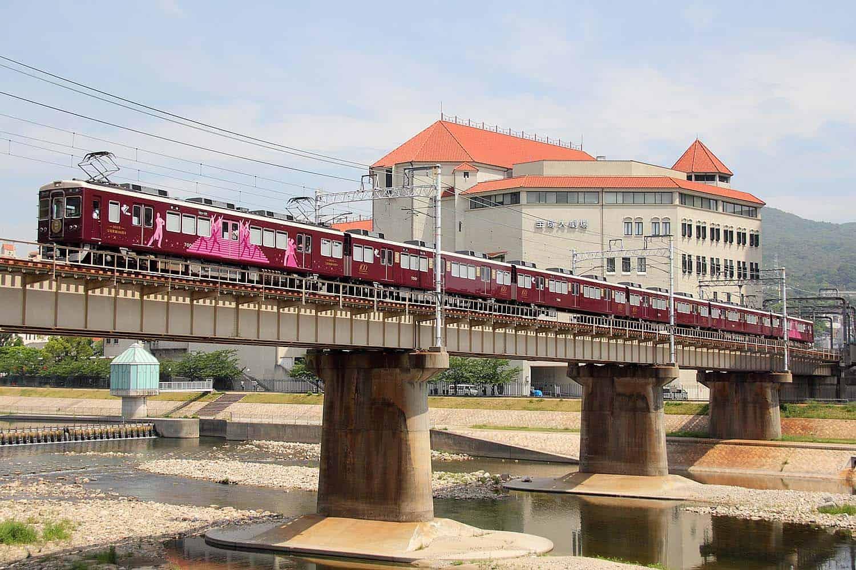 รถไฟฮันคิวที่วิ่งข้ามแม่น้ำมุโกะโดยมีฉากหลังเป็นโรงละครทาคาระซึกะ (Takarazuka)